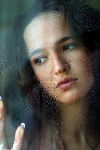64-133-woman-with-sad-smile-behind-a-wet-window